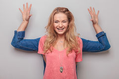 Smiling young woman holding her hand behind Royalty Free Stock Image