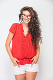 Smiling young woman holding her hands in pockets. While looking at the camera Stock Images