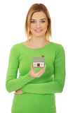 Smiling young woman holding house model Stock Photo