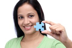 Smiling young woman holding jigsaw puzzle piece Stock Images