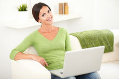 Smiling young woman holding a laptop. While looking at the camera stock image