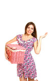 Smiling young woman holding a laundry basket on white background Stock Images