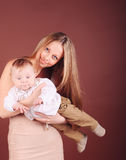 Smiling young woman holding little baby in studio Stock Photography