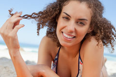 Smiling young woman holding a lock of hair with her fingers Stock Images