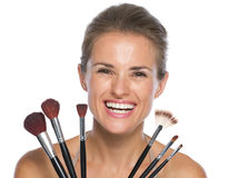 Smiling young woman holding makeup brushes Stock Image