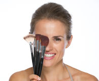 Smiling young woman holding makeup brushes in front of eye Stock Images
