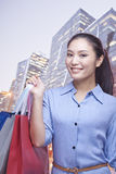 Smiling young woman holding many shopping bags, looking at camera Stock Photos