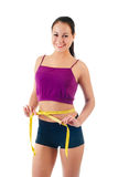 Smiling young woman holding a measure tape around her waist Stock Images