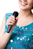 Smiling young woman holding microphone, close up. Smiling young female in sparkling blue dress, singing, holding microphone, close-up of mic, isolated on white royalty free stock photography