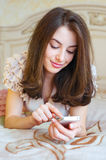 Smiling young woman holding mobile indoor Stock Images