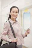 Smiling young woman holding mobile phone Royalty Free Stock Image