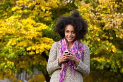 Smiling young woman holding mobile phone outdoors Royalty Free Stock Photography