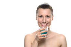 Smiling Young Woman holding Mouthwash in a glass Royalty Free Stock Photos