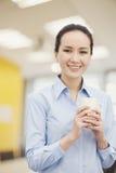 Smiling young woman holding mug, portrait Royalty Free Stock Image
