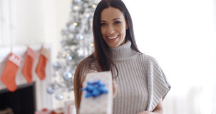Smiling young woman holding out a Christmas gift Royalty Free Stock Images