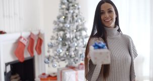 Smiling young woman holding out a Christmas gift stock video footage
