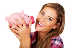 Smiling young woman holding piggybank Stock Photo