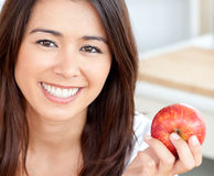 Smiling young woman holding a red an apple Royalty Free Stock Photo