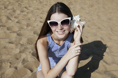 Smiling young woman holding shell on ear. On the sand beach. Call to me Royalty Free Stock Photos