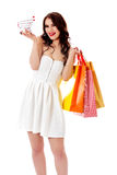 Smiling young woman holding small empty shopping cart and shopping bags Royalty Free Stock Image