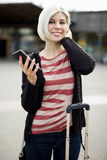 Smiling Young Woman Holding Smart Phone Outside Railroad Station Stock Images
