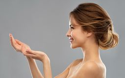 Smiling Young Woman Holding Something Imaginary Royalty Free Stock Photography