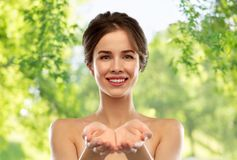 Smiling young woman holding something imaginary royalty free stock photo