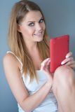 Smiling young woman holding a tablet Royalty Free Stock Photos