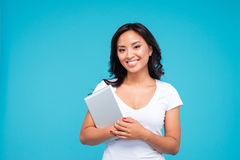 Smiling young woman holding tablet computer and looking at camera. Isolated on a blue background Royalty Free Stock Photo