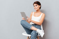 Smiling young woman holding tablet pc computer isolated Royalty Free Stock Images