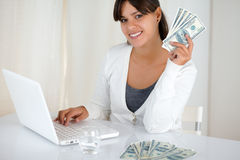Smiling young woman holding up cash money. Portrait of a smiling young woman holding up cash money in front of her laptop while is looking at you Royalty Free Stock Images