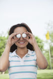 Smiling young woman holding up golf balls in front of her eyes Royalty Free Stock Image