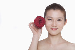 Smiling young woman holding up a red rose next to her ear, studio shot Stock Photo