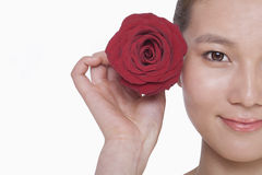 Smiling young woman holding up a red rose next to her ear, studio shot Royalty Free Stock Photography