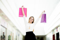Smiling young woman holding up shopping bags with joy Royalty Free Stock Photos