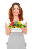 Smiling young woman holding vegetables Stock Photo