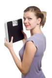 Smiling young woman holding a weight scale stock image