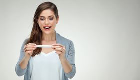 Smiling young woman holding white pregnant test. Isolated studio portrait of happy girl royalty free stock photos