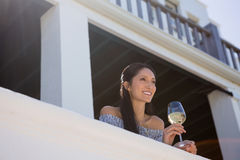 Smiling young woman holding white wine glass in balcony at restaurant Stock Images