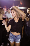 Smiling young woman holding wineglass while dancing at nightclub. Smiling young woman with eyes closed holding wineglass while dancing at nightclub Royalty Free Stock Photography