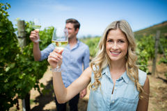 Smiling young woman holding wineglass at vineyard Royalty Free Stock Photos