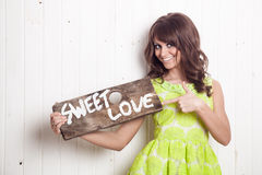Smiling young woman holding wooden banner Royalty Free Stock Images