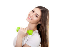 Smiling young woman holds green colored dumbbell Stock Photography