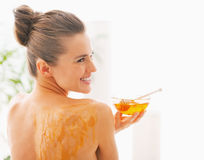 Smiling young woman with honey plate sitting on massage table Royalty Free Stock Photography