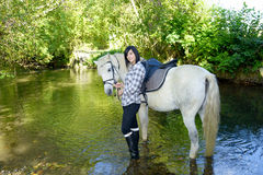 Smiling young woman with horse in the river royalty free stock photography
