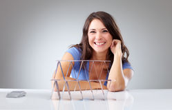 Smiling young woman with a house of cards Stock Photos