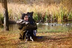 Young woman with border collie dog in the autumn park. Smiling young woman hugging her border collie dog Royalty Free Stock Image