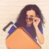 Smiling young woman hugging her orange suitcase. Casual girl is ready to travel. Happy woman in sunglasses dreaming about vacation royalty free stock image