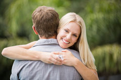 Smiling young woman hugging man Royalty Free Stock Images