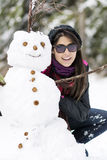 Smiling young woman hugging   snowman Stock Photos
